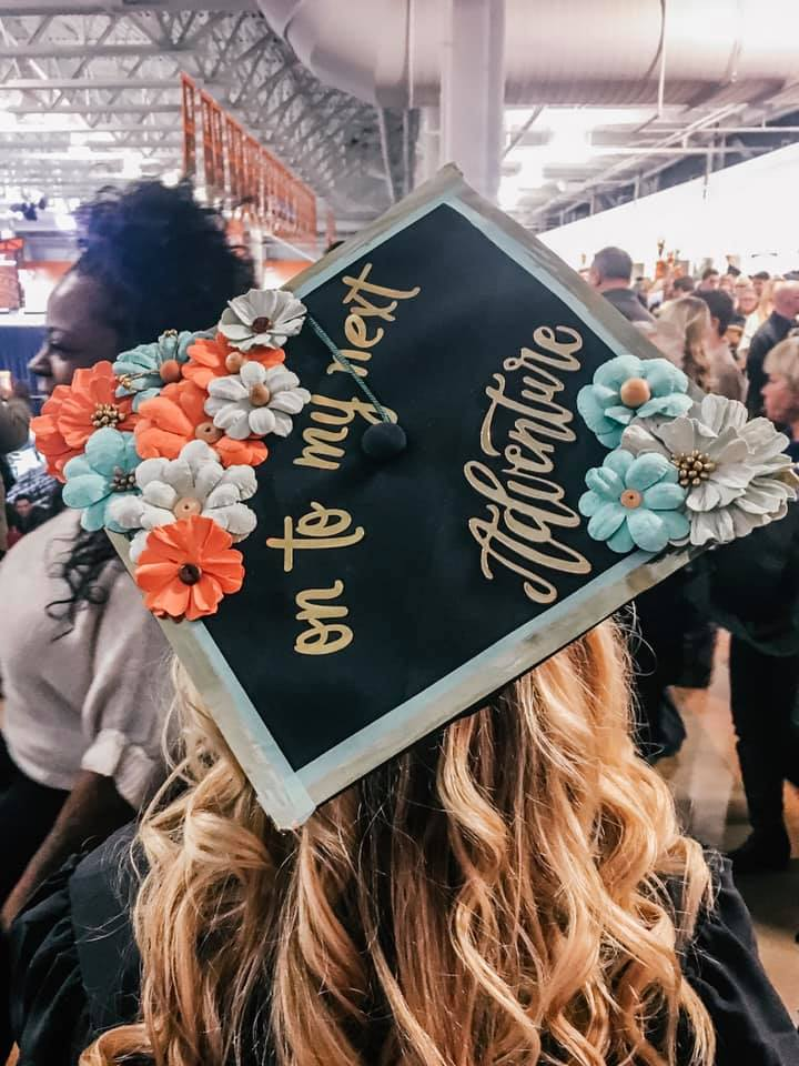 """back of woman's head at a graduation showing graduation cap that has blue and coral flowers with the words """"on to my next adventure"""" in the center"""