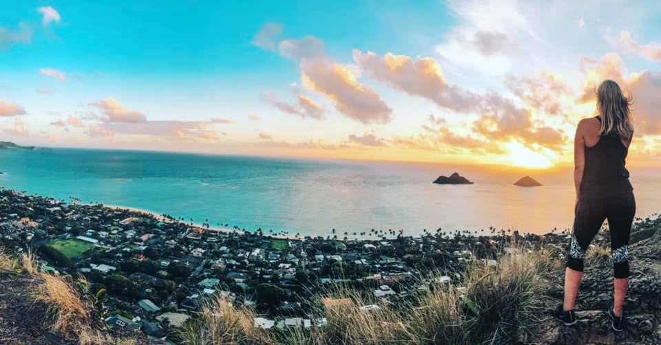 Woman looking out at Lanikai Beach as she is on the edge of Lanikai Pillbox trail at sunrise.