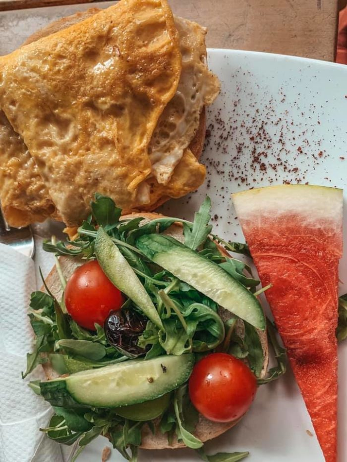 a white plate with scrambled eggs, watermelon, and an arugula salad