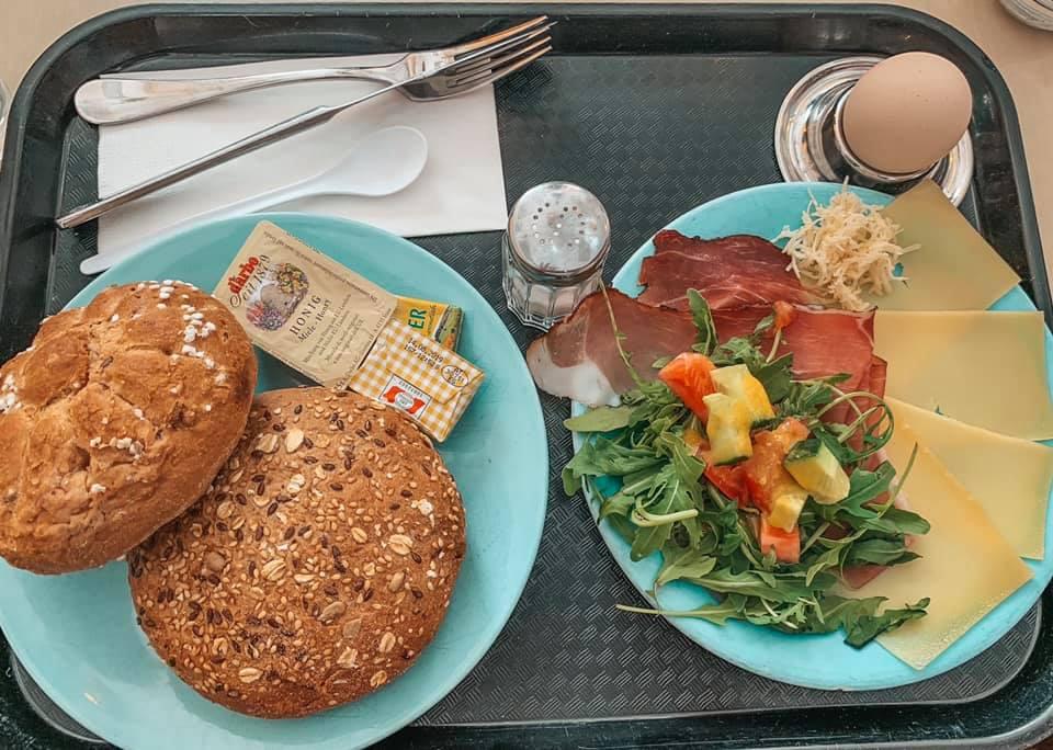 tray of Austrian breakfast cuisine including: multi grain bread, arugula salad, assortment of cheese, prosciutto, and a soft boiled egg