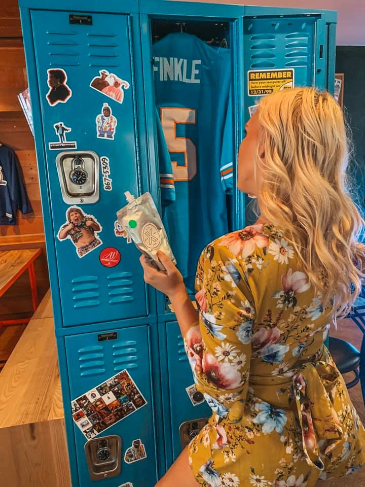A woman in a yellow floral dress holding an adult capri sun looking into a bright blue locker