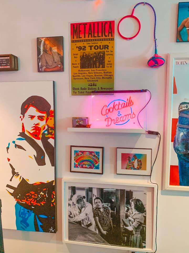 White wall covered with Ferris Buehler and other throwback references, as well as a neon sign that reads Cocktails & Dreams