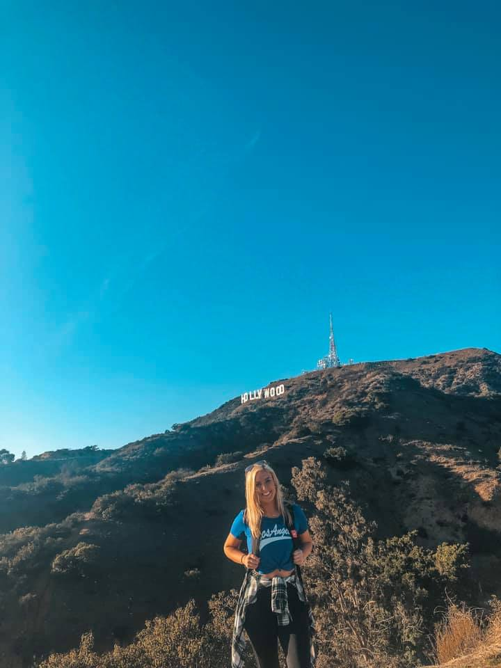 Solo traveler standing in front of Hollywood sign in Los Angeles