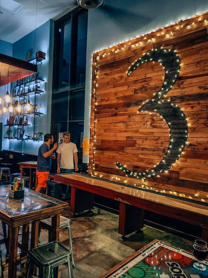 Wall covered with the number 3 outlined in lights.  Game of shuffleboard being played in front.