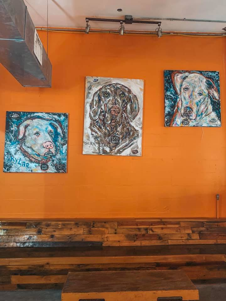 An orange wall with three somewhat abstract paintings of three different breeds of dogs.