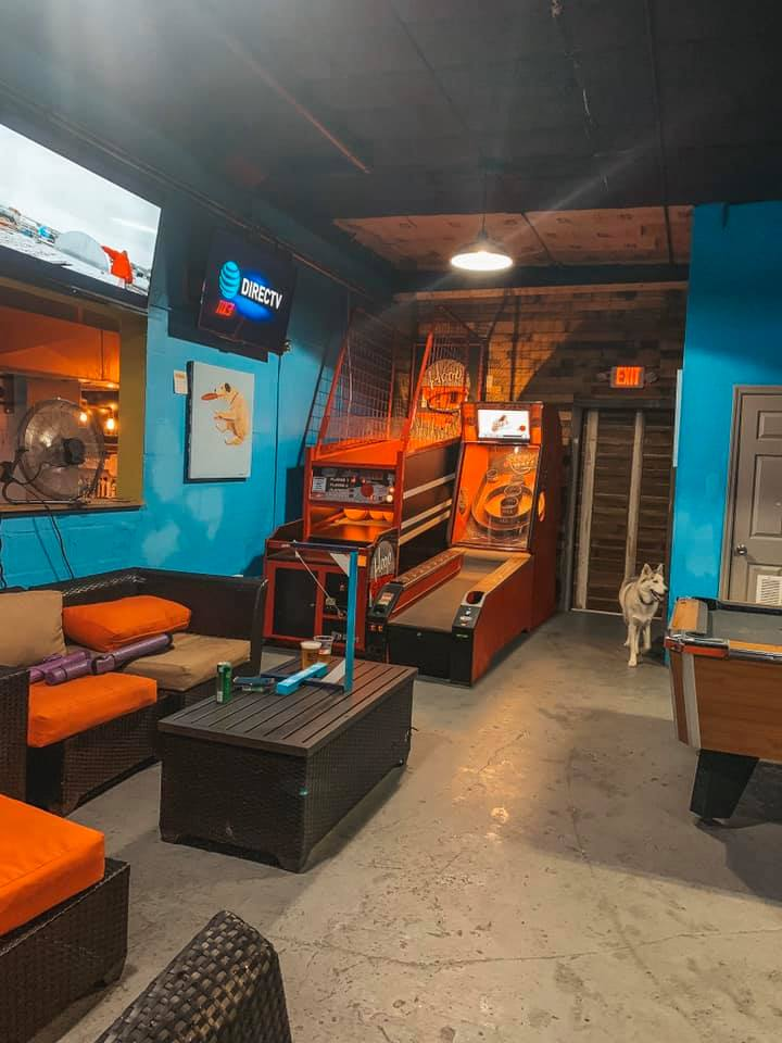 A blue room with seating as well as pool, skeeball, and basketball.  As well as a husky wandering around.