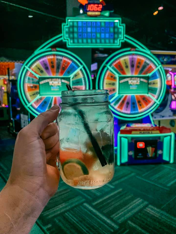 A hand holding up a watermelon and mint sangria in front of a wheel of fortune game