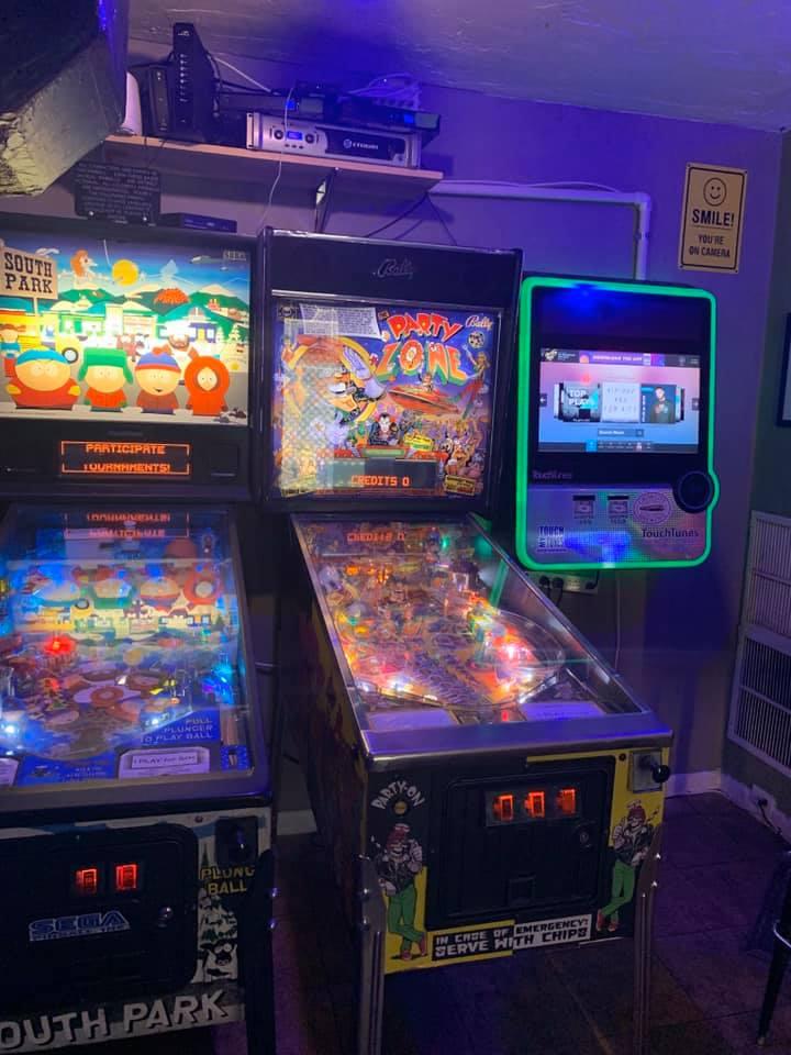 2 pinball machines next to a touchtunes jukebox