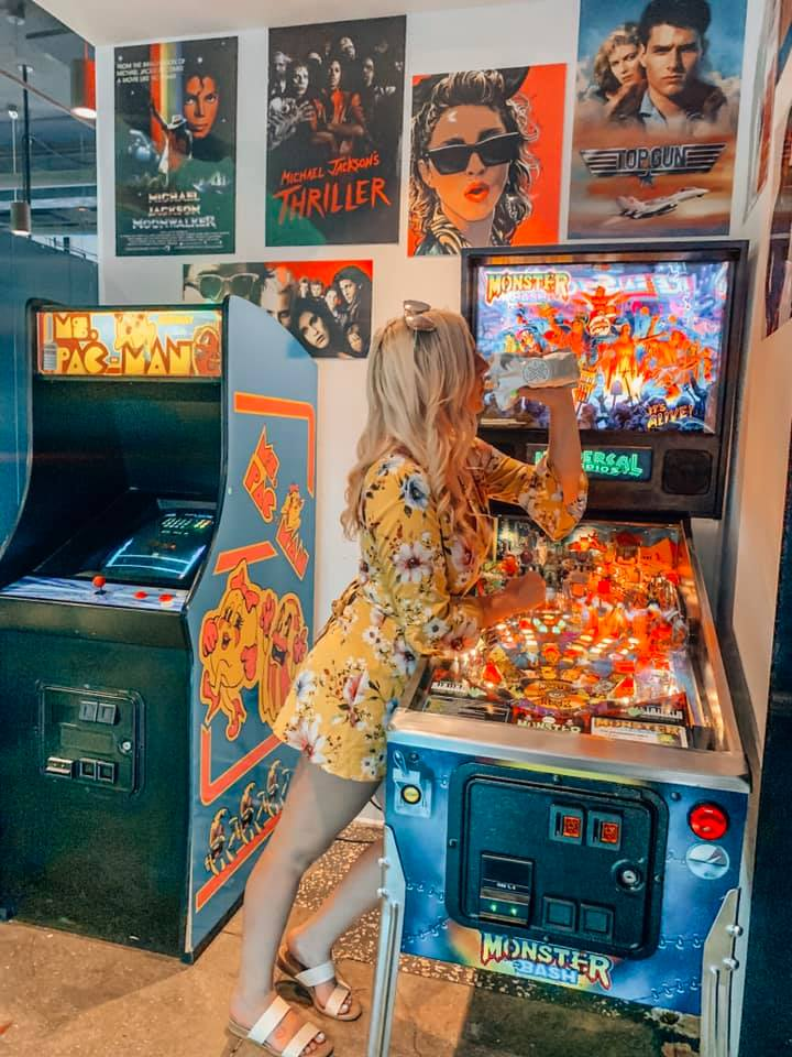 a woman in a yellow floral dress leaning against a pinball machine drinking an adult capri sun