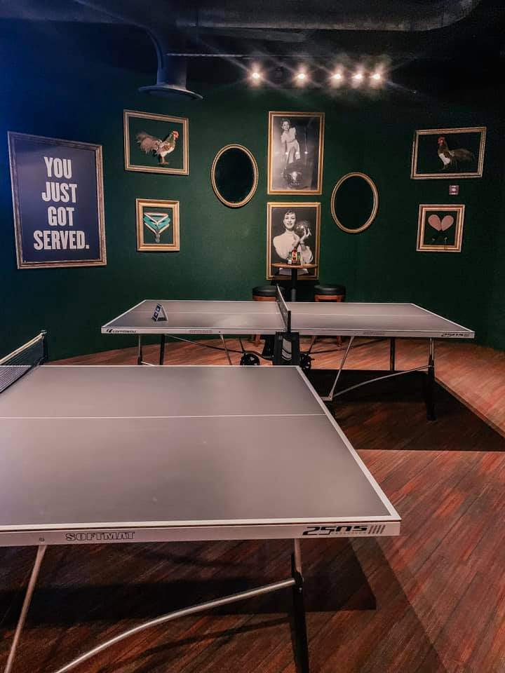 two ping pong tables set up in a green room with portrait covered walls