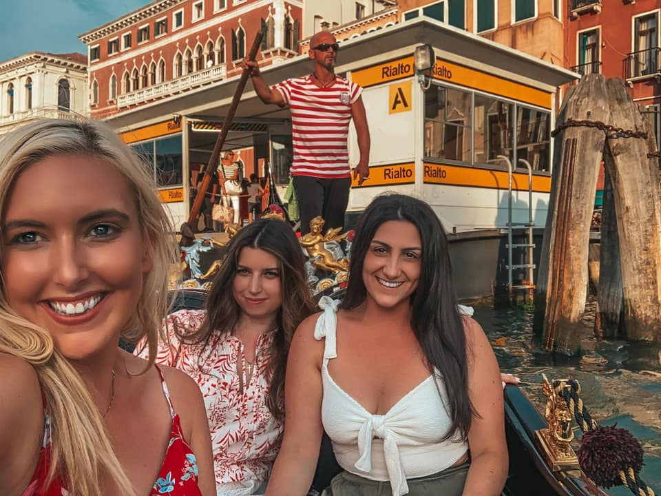 Three girls taking a selfie in a gondola in Venice, Italy. Meeting friends while traveling solo