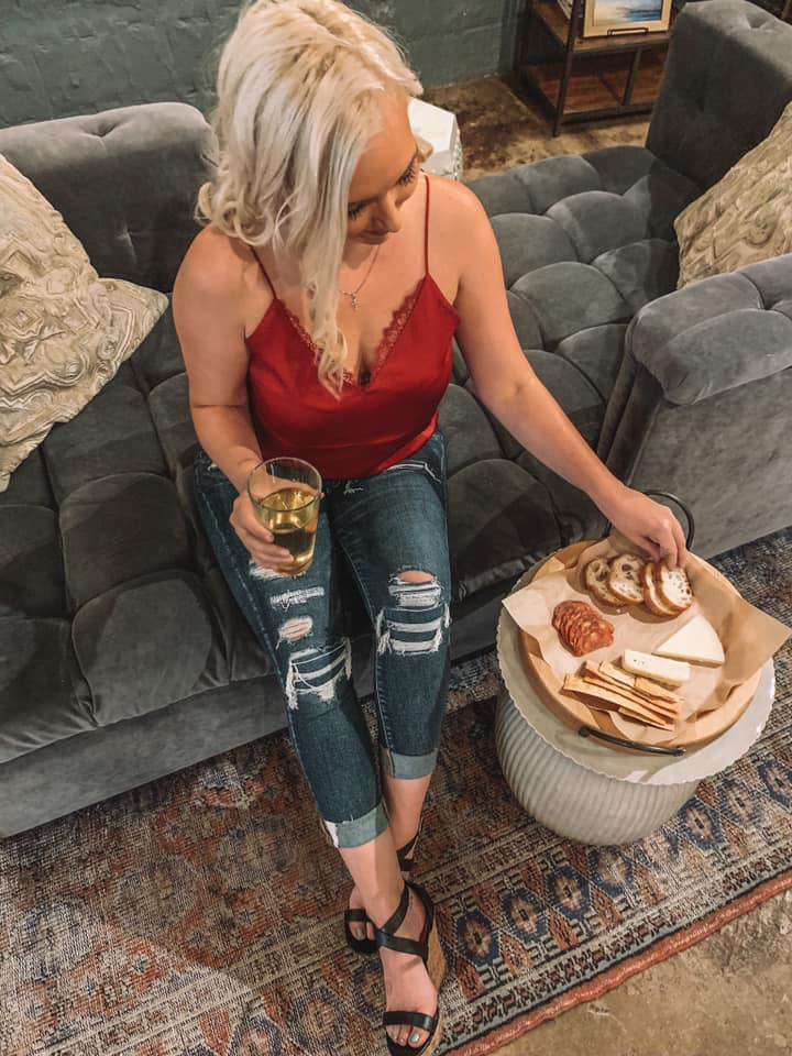 above shot of woman in red top grabbing a piece of pita off of a charcuterie board