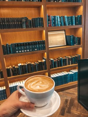 holding latte in front of book shelf full of blue books at coffee shops in St. Petersburg, Florida