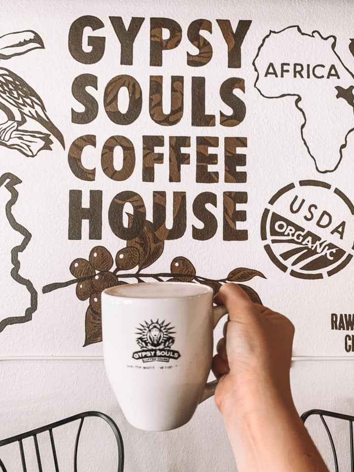 """coffee mug that says """"gypsy souls"""" being held up in front of wall mural that says """"gypsy souls coffee house"""""""