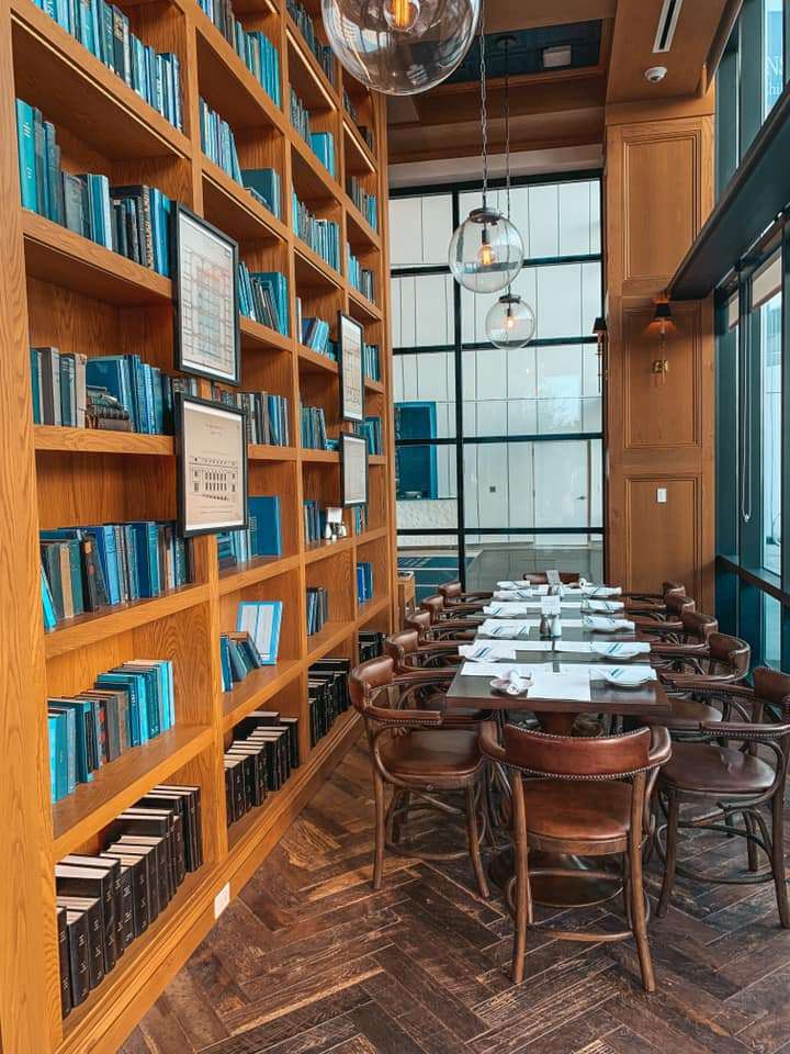 blue books lining bookshelves behind a dining area
