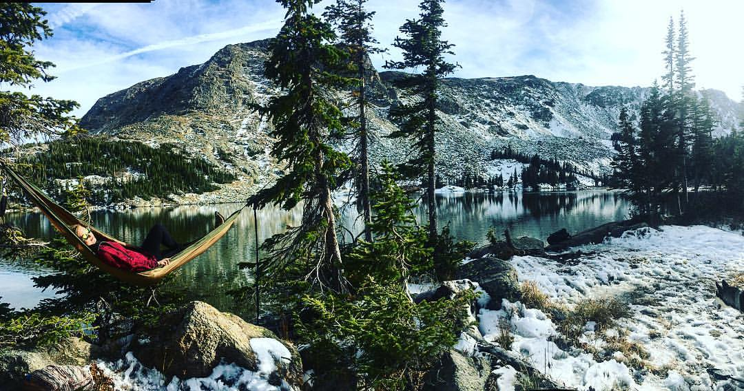 Woman laying hammock on the top of Colorado mountains surrounded by trees and a lake. This is how to travel more!