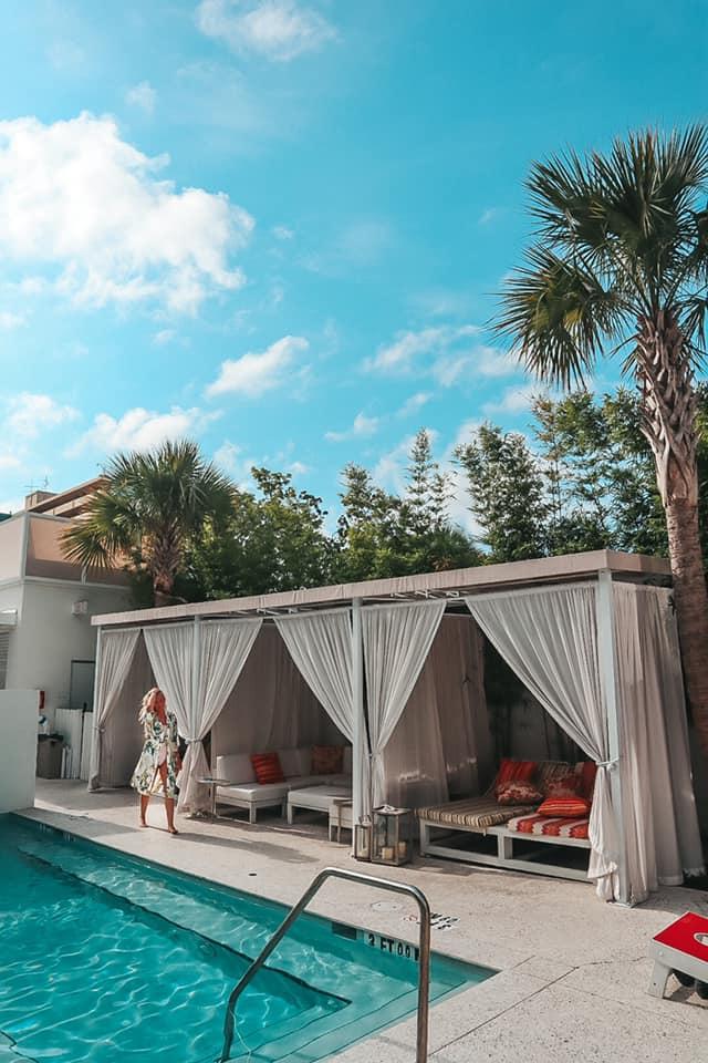 Woman walking along the pool and cabanas at Sarasota Modern in Sarasota, Florida