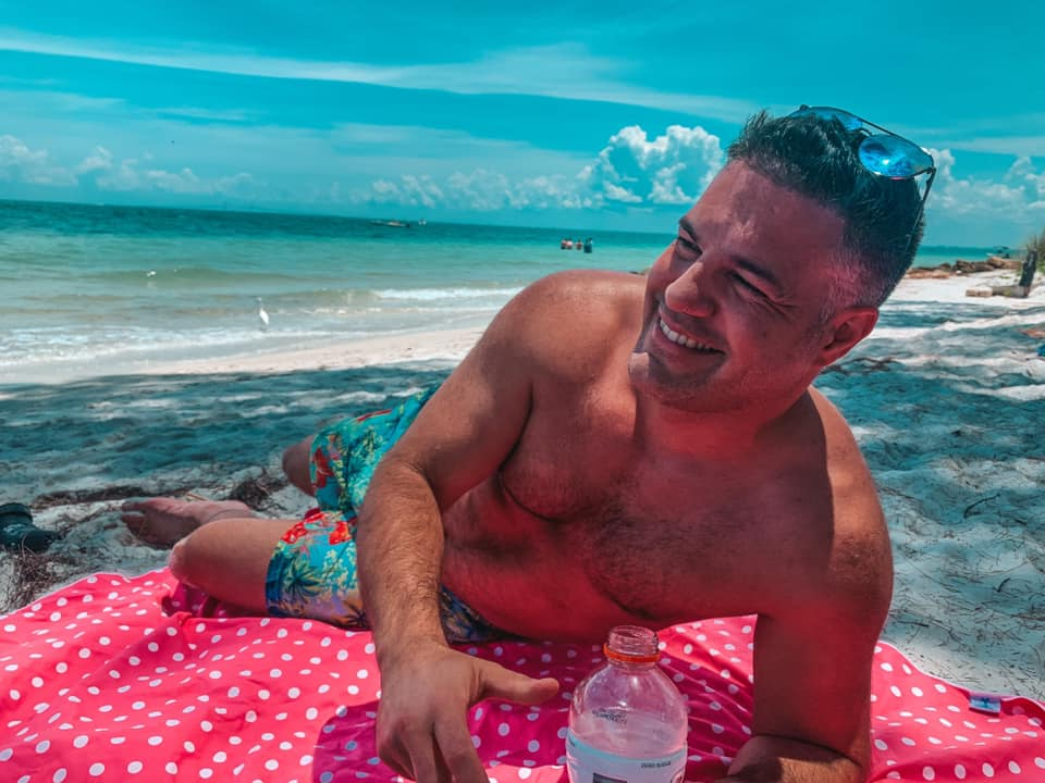Man smiling while laying out on the Florida Beach