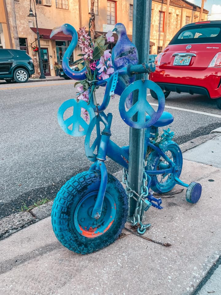 Purple painted tricycle locked up to a street sign