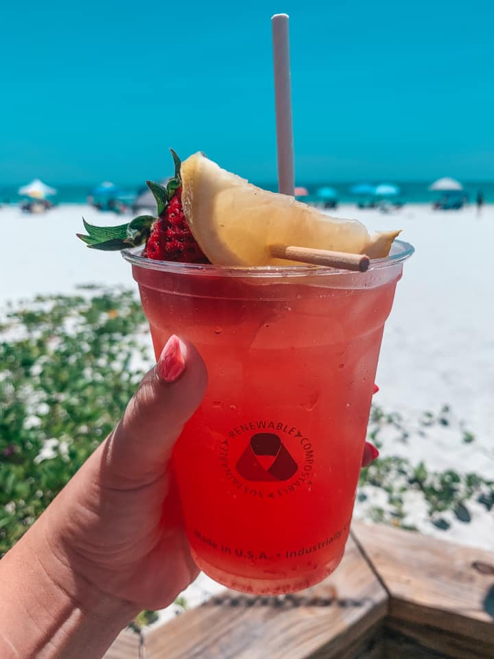 Fun fruity drink being held up in front of the beach