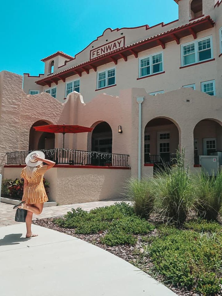 woman kicking her leg up and holding her hat and suitcase while looking at the beautiful Fenway Hotel in Dunedin, Florida