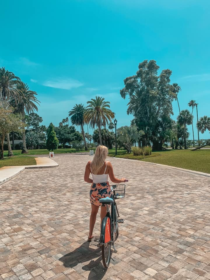 Woman standing next to and holding bicycle while looking out at Dunedin, Florida