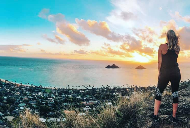 Woman standing near the edge of the Lanikai Pillbox trail looking out at Lanikai Beach at sunrise