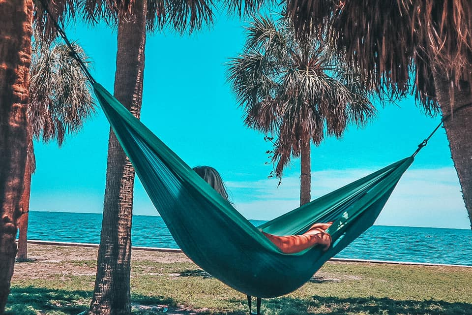Woman relaxing on a green hammock held up by two palm trees