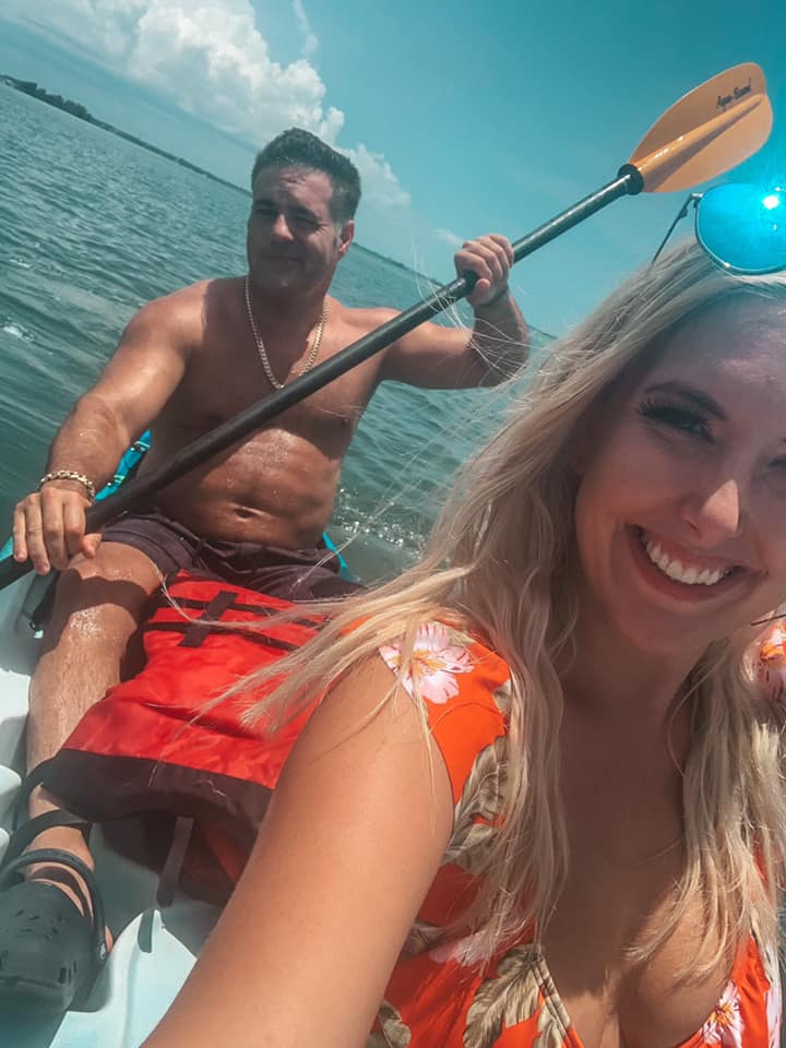 Couple smiling while kayaking through the ocean in Florida.