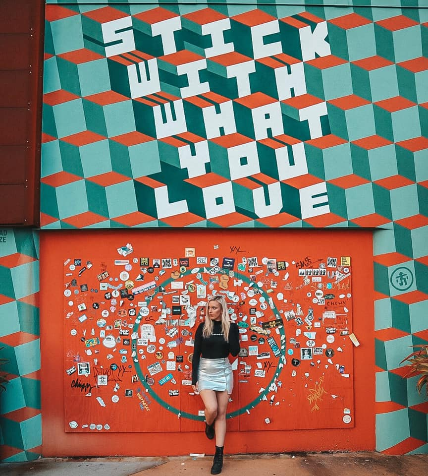 "Woman leaning up against a mural in downtown St. Pete that says ""Stick with what you love"""