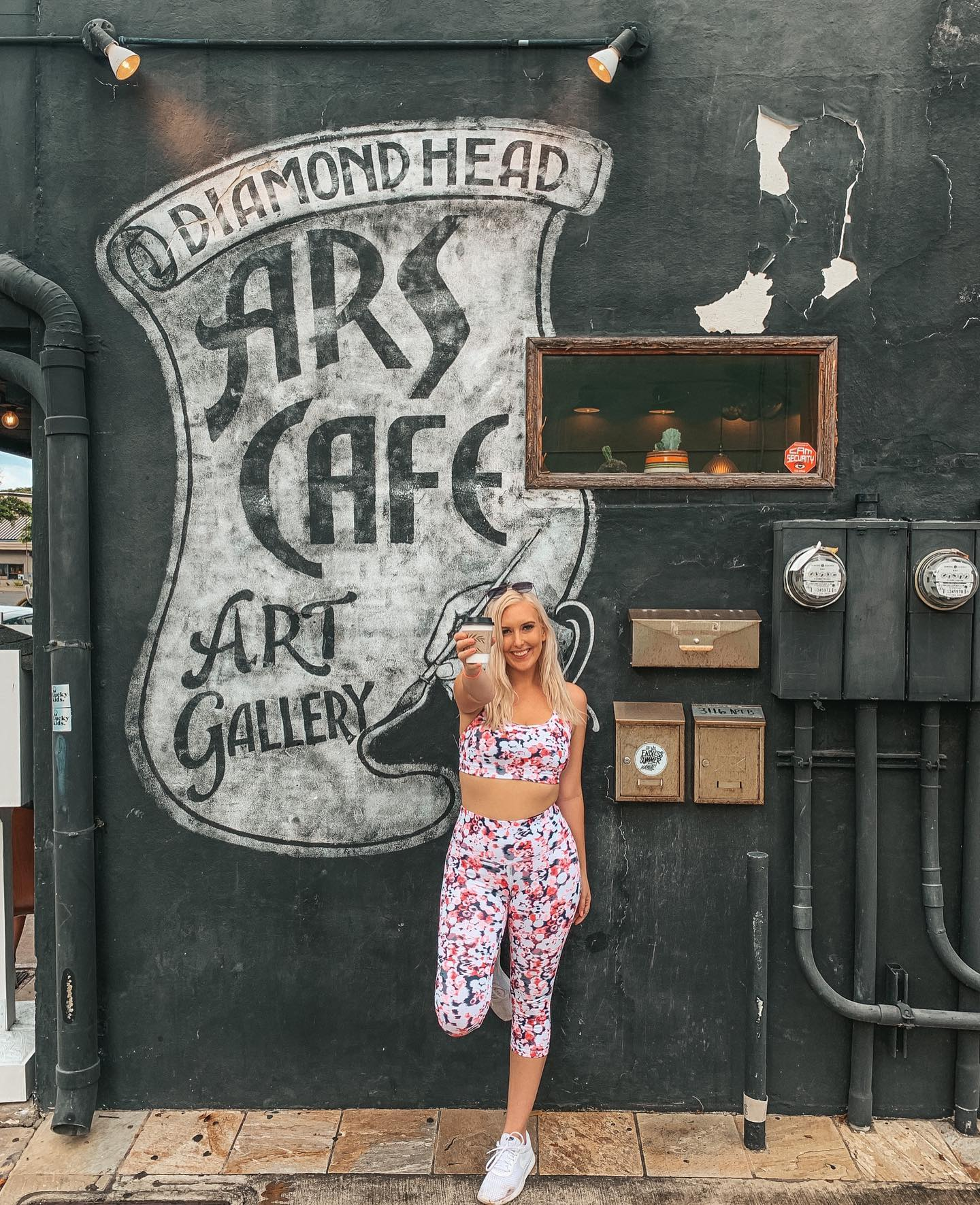 "Destiny wearing a pink speckled workout outfit and holding up coffee outside of Ars Cafe in front of their mural that reads ""Diamond Head Ars Cafe Art Gallery"""