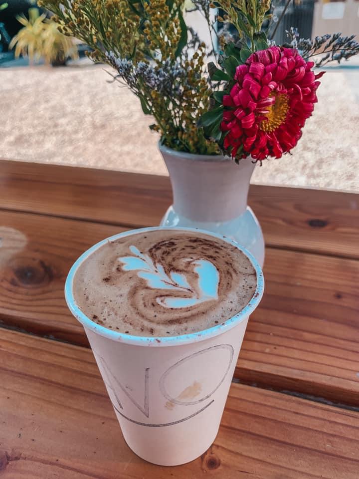 Arvo latte art near a vase of flowers