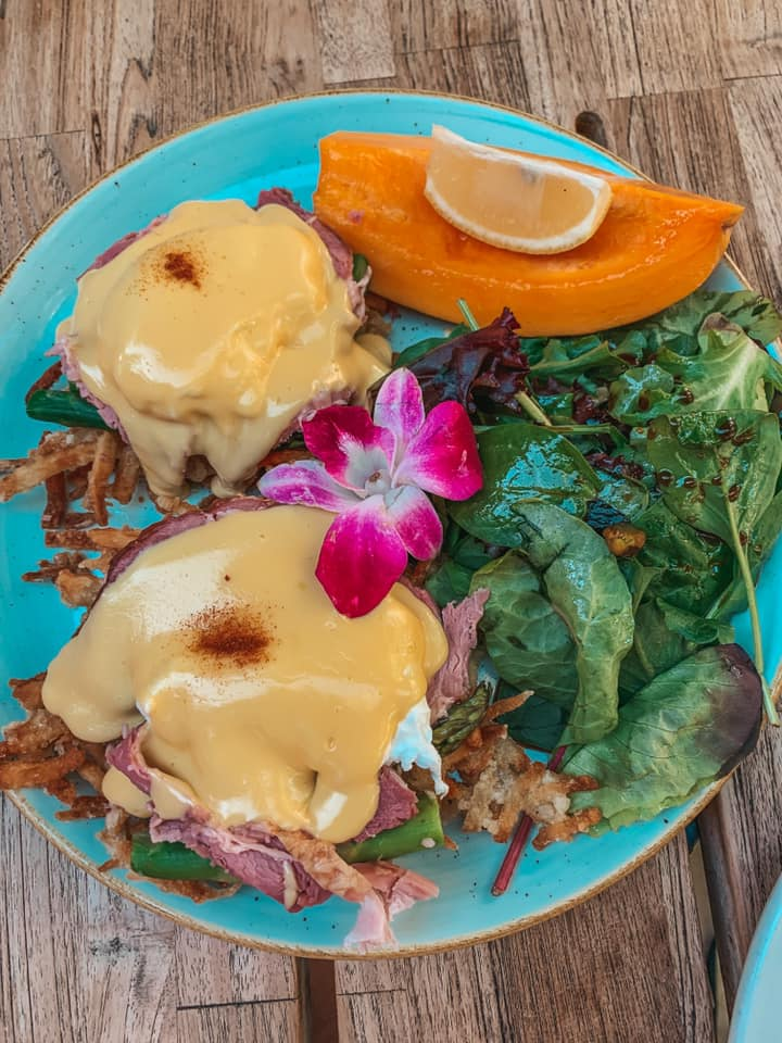 Eggs benedict, some greens, and a mango beautifully plated from Island Vintage Coffee