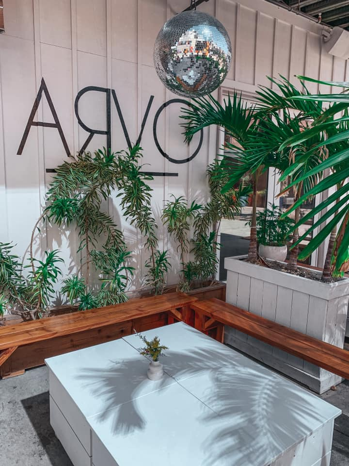 Outdoor seating area at Arvo. Brown benches, a beautiful white table, plenty of hanging and sitting plants, as well as a disco ball.