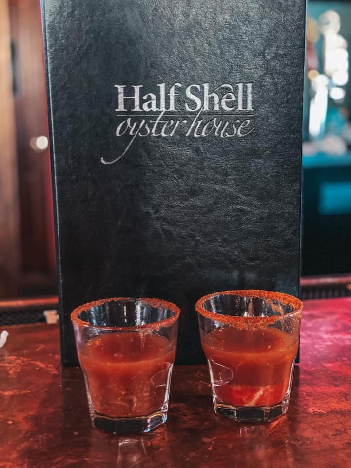 Two oyster shooters with an Old Bay rim in front of Half Shell Oyster House menu