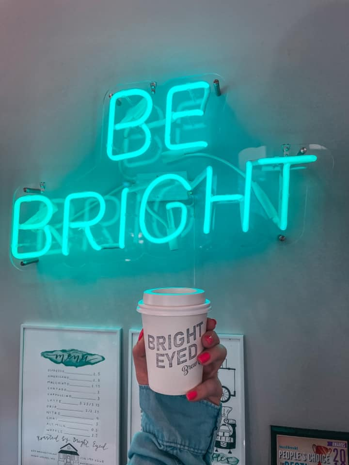 "Holding up coffee from bright eyed brew co in front of a neon sign that reads ""be bright"""