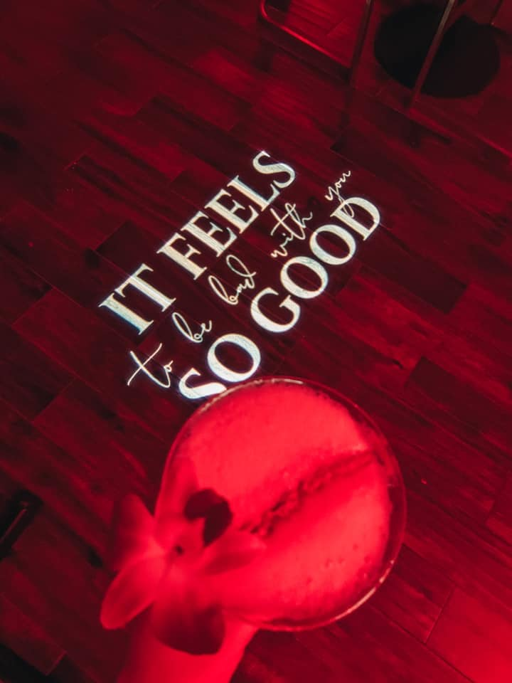 """holding """"sloth"""" drink over a quote being projected on the floor with red lighting """"It feels so good to be bad with you"""""""