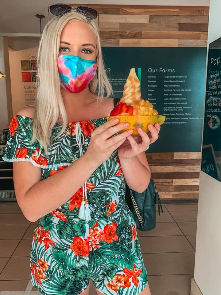 holding banan up in a papaya boat