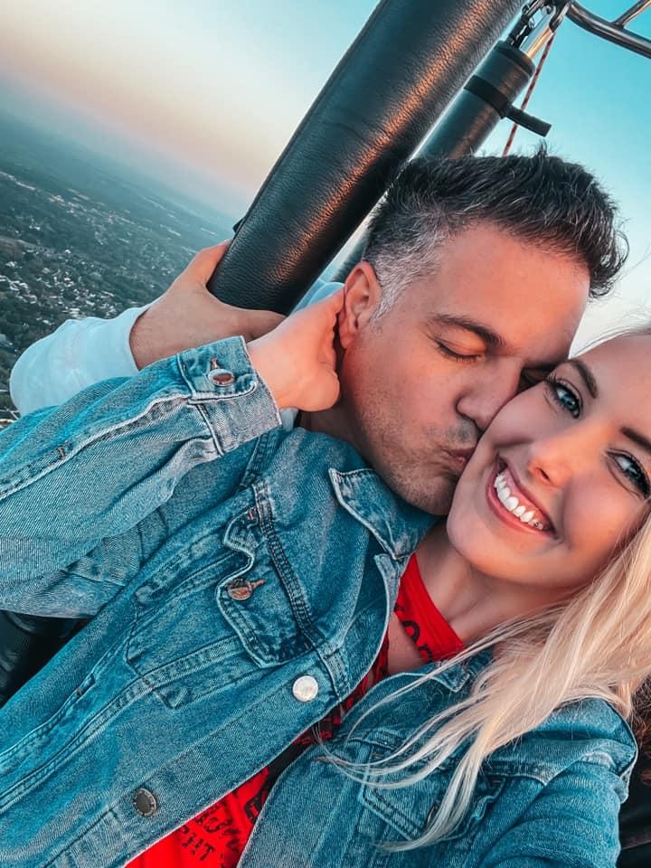 boyfriend kissing girlfriend on the cheek in the hot air balloon