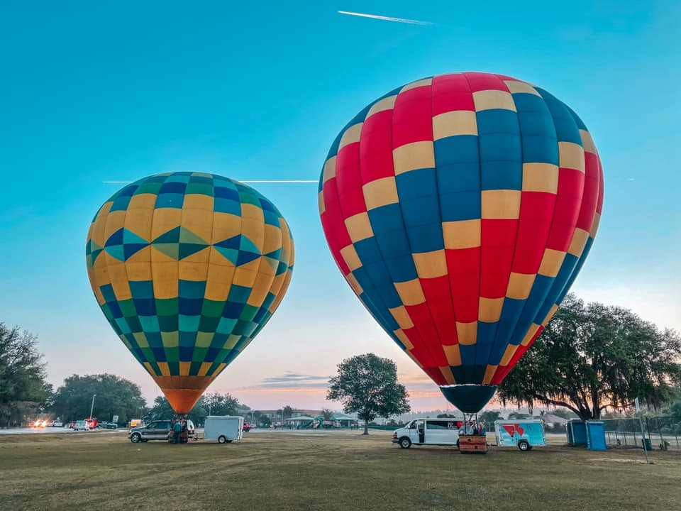 Two hot air balloons on the ground preparing to take off in Tampa Bay